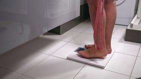 Mujer joven que mide su peso en una escala almacen de metraje de vídeo
