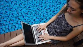 Mujer joven que miente cerca de piscina azul y que usa el ordenador portátil en la cámara lenta metrajes