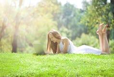 Mujer joven que miente con el ordenador portátil en el prado verde hermoso Fotografía de archivo libre de regalías