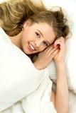 Mujer joven que miente en cama Fotografía de archivo libre de regalías