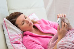 Mujer joven que miente en cama Foto de archivo libre de regalías