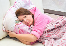 Mujer joven que miente en cama Foto de archivo