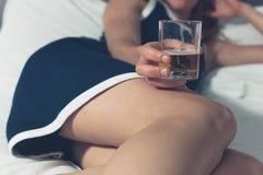 Mujer joven que miente en cama con el vidrio en su mano fotos de archivo