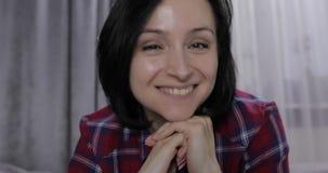 Mujer joven que miente en cama y que tiene charla video usando webcam en el ordenador port?til almacen de video