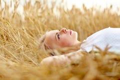 Mujer joven que miente en campo y el sueño de cereal Foto de archivo