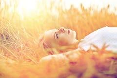 Mujer joven que miente en campo y el sueño de cereal Imagen de archivo libre de regalías