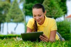 Mujer joven que miente en el césped con una tableta Foto de archivo