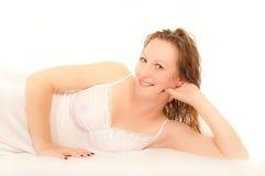 Mujer joven que miente en el camisón que desgasta de la cama Foto de archivo libre de regalías