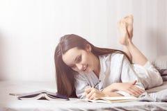 Mujer joven que miente en el dormitorio de la cama en casa y que escribe en el diario o que planea su día, haciendo el horario pa Fotografía de archivo