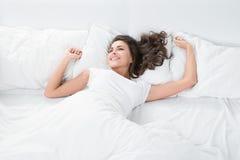 Mujer joven que miente en el lino blanco en cama Imagenes de archivo