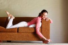 Mujer joven que miente en el sofá usando la tableta digital Fotos de archivo