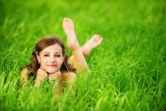 Mujer joven que miente en hierba Imagen de archivo