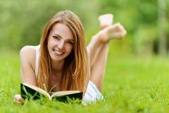 Mujer joven que miente en hierba Foto de archivo