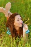 Mujer joven que miente en hierba Fotografía de archivo libre de regalías