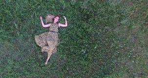 Mujer joven que miente en hierba almacen de video
