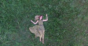 Mujer joven que miente en hierba almacen de metraje de vídeo
