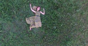 Mujer joven que miente en hierba metrajes