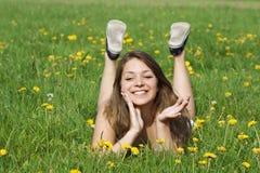 Mujer joven que miente en hierba verde fresca Foto de archivo libre de regalías