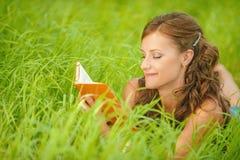 Mujer joven que miente en hierba y el libro de lectura Fotos de archivo
