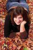 Mujer joven que miente en hojas de otoño Fotos de archivo libres de regalías
