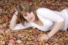 Mujer joven que miente en hojas de otoño Fotos de archivo