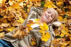 Mujer joven que miente en hojas de otoño Imagen de archivo