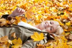 Mujer joven que miente en hojas de otoño Imagenes de archivo