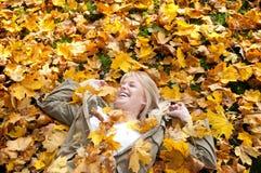 Mujer joven que miente en hojas de otoño Fotografía de archivo
