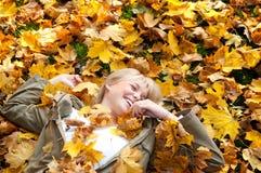 Mujer joven que miente en hojas de otoño Foto de archivo