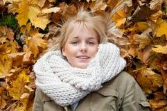 Mujer joven que miente en hojas de otoño Imágenes de archivo libres de regalías