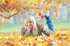 Mujer joven que miente en hojas de otoño Foto de archivo libre de regalías