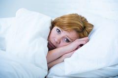 Mujer joven que miente en incapaz enfermo de la cama de dormir depresión sufridora y desorden durmiente del insomnio de las pesad Imagenes de archivo