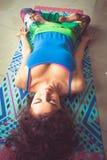 Mujer joven que miente en la estera con las piernas en tiro interior de la posición de loto Fotografía de archivo