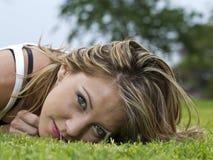 Mujer joven que miente en la hierba Foto de archivo libre de regalías
