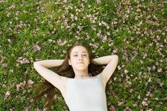 Mujer joven que miente en la hierba Imágenes de archivo libres de regalías