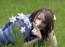 Mujer joven que miente en la hierba con los narcisos Foto de archivo libre de regalías