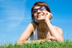 Mujer joven que miente en la hierba verde Foto de archivo libre de regalías