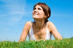 Mujer joven que miente en la hierba verde Foto de archivo