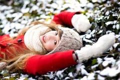 Mujer joven que miente en la nieve Foto de archivo