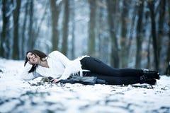 Mujer joven que miente en la nieve Fotos de archivo libres de regalías