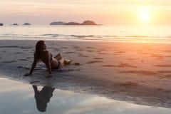 Mujer joven que miente en la playa durante puesta del sol Foto de archivo libre de regalías