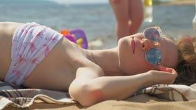 Mujer joven que miente en la playa metrajes
