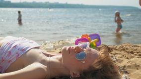 Mujer joven que miente en la playa almacen de metraje de vídeo