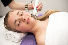 Mujer joven que miente en la tabla del masaje que recibe masaje de cara Fotografía de archivo