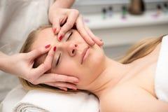 Mujer joven que miente en la tabla del masaje que recibe masaje de cara beaut Fotos de archivo libres de regalías