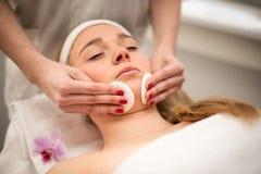 Mujer joven que miente en la tabla del masaje que recibe masaje de cara beaut Imagenes de archivo