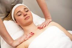 Mujer joven que miente en la tabla del masaje que recibe masaje de cara beaut Foto de archivo