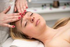 Mujer joven que miente en la tabla del masaje que recibe masaje de cara beaut Fotografía de archivo libre de regalías