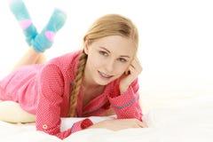 Mujer joven que miente en los pijamas que llevan de la cama Imagen de archivo libre de regalías
