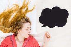 Mujer joven que miente en los pijamas que llevan de la cama Imagenes de archivo